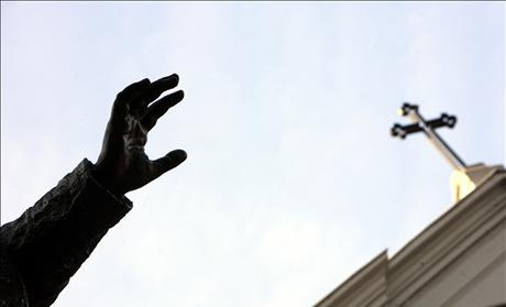 Hand of statue of Pope Benedict XV, seen under cross of St. Esprit Cathedral in Istanbul 