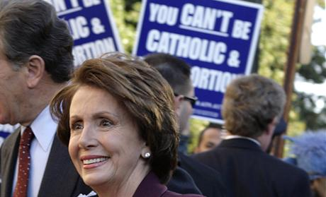 U.S. Speaker of the House elect Pelosi and her husband walk past abortion protesters as they arrive for an interfaith prayer service for House leadership in Washington