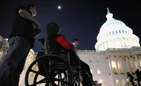 A woman in a wheelchair and her son are just a few of thousands of protestors remain late in the evening after a 'Kill the Bill' rally against Obama's health care legislation, on the grounds of the US Capitol in Washington