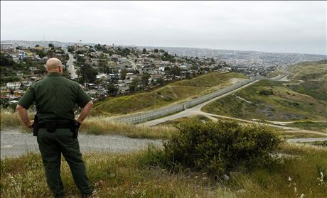 United States border patrol agent looks across the fence at Mexico as he patrols the U.S. border in San Ysidro, California,