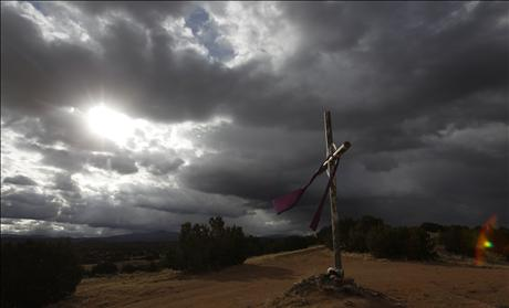 A cross is seen on the hill as the sun rises on Easter morning in Chimayo