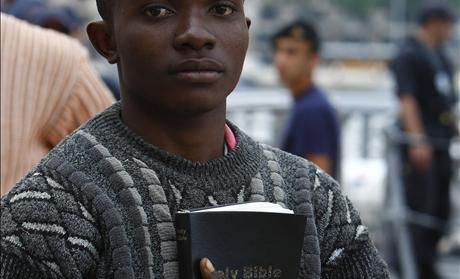 African immigrant carrying a bible disembarks from an Armed Forces of Malta patrol boat after arriving in Valletta&#39;s Marsamxett Harbour 