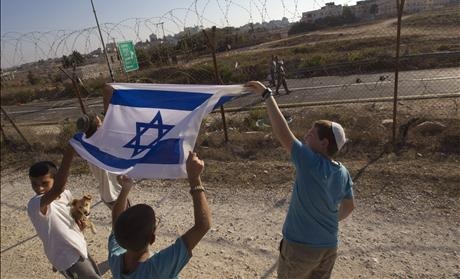 Jewish settler boys hold up an Israeli flag next to the fence of the West Bank settlement of Beit El as Palestinians walk past