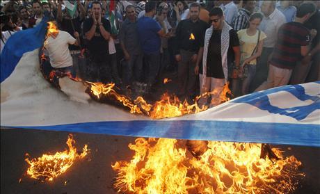 Palestinian protesters burn an Israeli flag