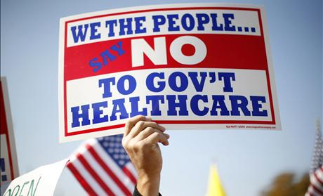 A demonstrator holds up a sign at a rally on healthcare on Capitol Hill in Washington - ObamaCare