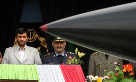 Iranian President Ahmadinejad watches as missile passes by during Army Day military parade in Tehran