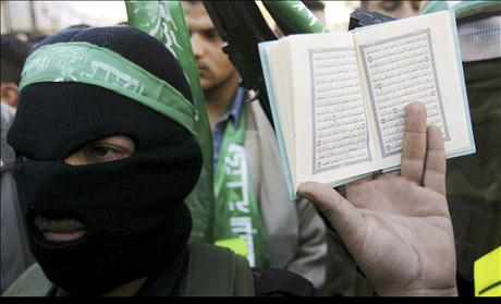 A Palestinian man holds a Koran as a members of the Islamic group Hamas look on during a protest in Nablus