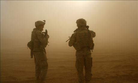 A U.S. soldier stand walk in a cloud of dust as a Blackhawk helicopter takes off during a mission in southern Baghdad