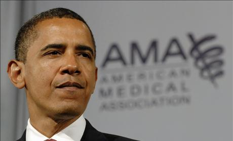 Obama pauses during a speech on health care to the American Medical Association in Chicago, Illinois