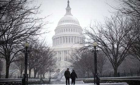 A couple walks on the grounds of the U.S. Capitol Building during a snow storm in Washington