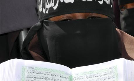 A pro Al-Shabaab female demonstrator holds a copy of the Koran during a protest against the burning of the Islamic holy book in Mogadishu