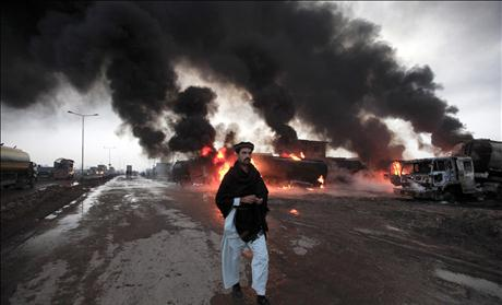 A fire fighter gestures in front of burning oil tankers which were attacked by unidentified gunmen on the outskirts of Peshawar