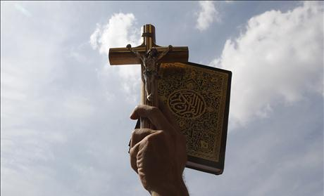 An Egyptian holds up a Koran and a cross during a rally to demonstrate the unity between Muslims and Christians at Tahrir Square in Cairo