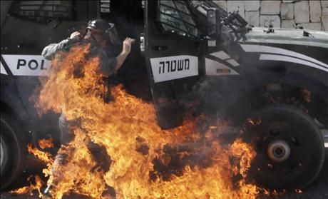 An Israeli border police officer is engulfed by flames after a petrol bomb was thrown at him during clashes with Palestinians in the mostly Arab neighborhood of Silwan in East Jerusalem