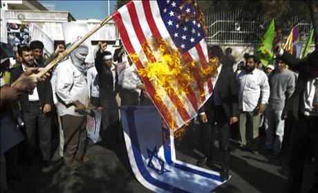 Iranian students burn a U.S. flag during a rally in support of the Bahraini nation in front of Bahrain's embassy in Tehran