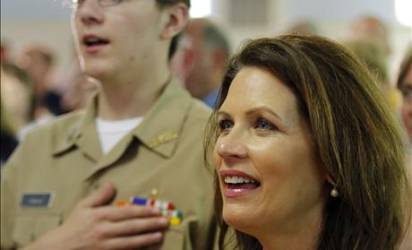 U.S. Congresswoman and likely Republican presidential candidate Michele Bachmann sings 'God Bless America' next to a current member of the U.S. Navy at an event to pay tribute to veterans on Memorial Day in Dover