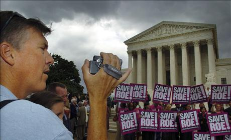 A tourist makes home movies of the crowd gathered at the US Supreme Court in Washington.