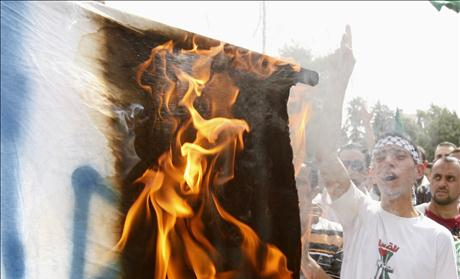 Jordanian supporters of opposition parties burn an Israeli flag and shout anti-Israel slogans during a demonstration in Amman