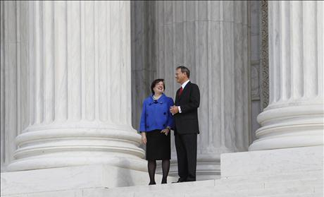 U.S. Supreme Court Justice Elena Kagan stands outside of the Supreme Court building with Chief Justice of the United States John Roberts after her investiture ceremony in Washington