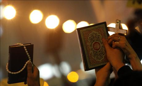 Egyptian Muslims and Christians hold a Koran and a cross in the Shobra district of Cairo