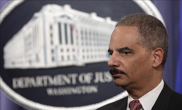 U.S. Attorney General Eric Holder pauses at a news conference at the Justice Department in Washington