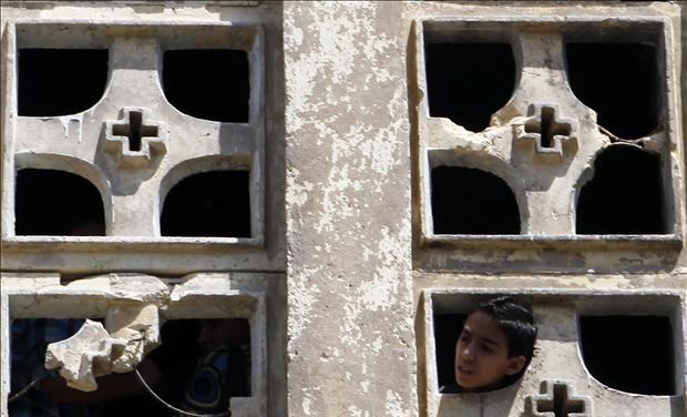 A Coptic Christian boy looks out of the Saint Mary Church which was set on fire during clashes between Muslims and Christians on Saturday in the heavily populated area of Imbaba in Cairo
