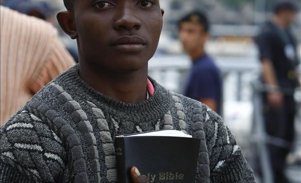 African immigrant carrying a bible disembarks from an Armed Forces of Malta patrol boat after arriving in Valletta's Marsamxett Harbour