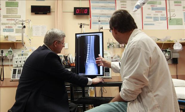 Canada's PM Harper examines an X-ray with Doctor Corkal at Stanton Territorial Hospital in Yellowknife