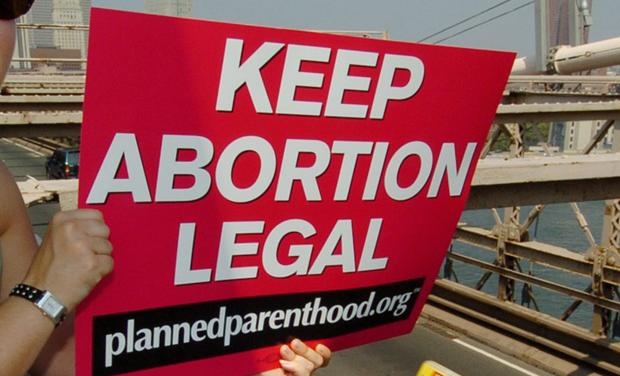 Planned Parenthood abortion rights protester signals Brooklyn Bridge traffic.