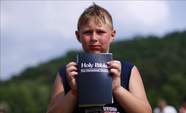 Boy with new bible after baptism during Creation08 Christian music festival in Mount Union Pennsylvania