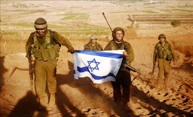 Israeli soldiers hold Israeli flag after leaving Lebanon near Israeli-Lebanon border