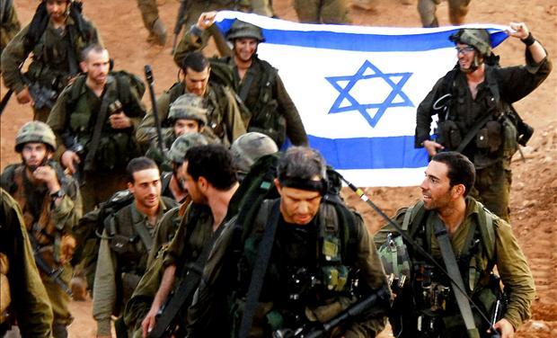Israeli soldiers hold an Israeli flag as they walk together after leaving Lebanon near the Israeli-Lebanon border