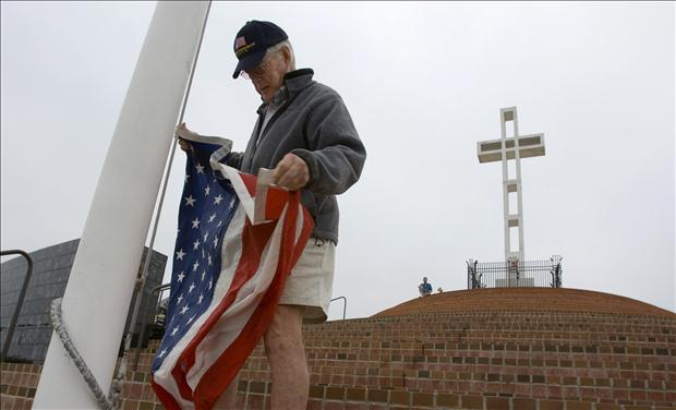 Clyde Rights raises flag next to Mount Soledad Cross which is being transferred to federal government ownership