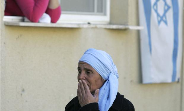 An Israeli woman stands near the scene of a suicide bombing in the southern town of Dimona