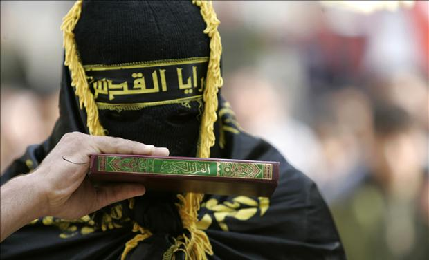 Palestinian militant from Islamic Jihad kisses copy of Koran in West Bank village of Qabateanear