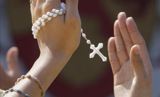 A woman, holding her rosary, claps her hands in time with music during a youth rally for Pope Benedict XVI in Yonkers New York