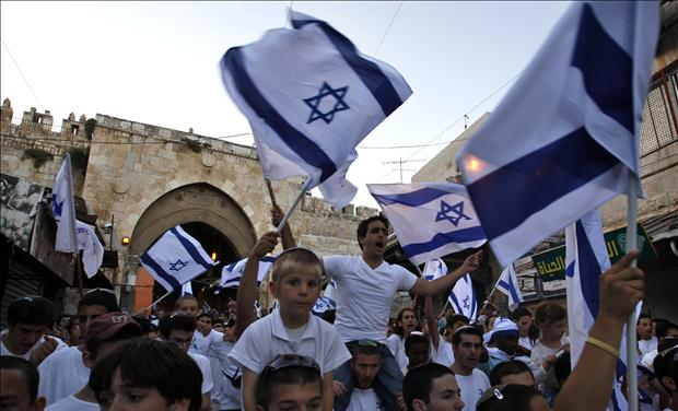 Israelis wave national flags during a parade marking Jerusalem Day in front of the Damascus Gate in Jerusalem's Old City