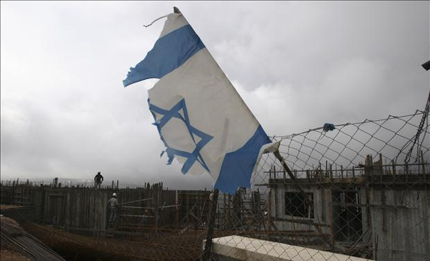 An Israeli national flag is seen as Palestinian labourers work on a building under construction in the Jewish settlement of Har Gilo