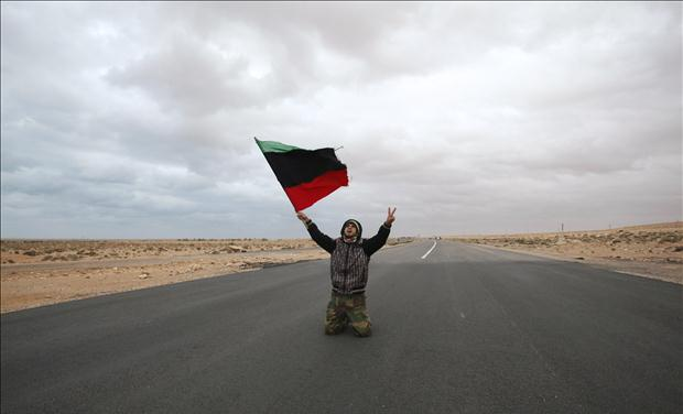 An anti-Gaddafi rebel prays and chants along a road during clashes with pro-Qaddafi forces near Ras Lanuf