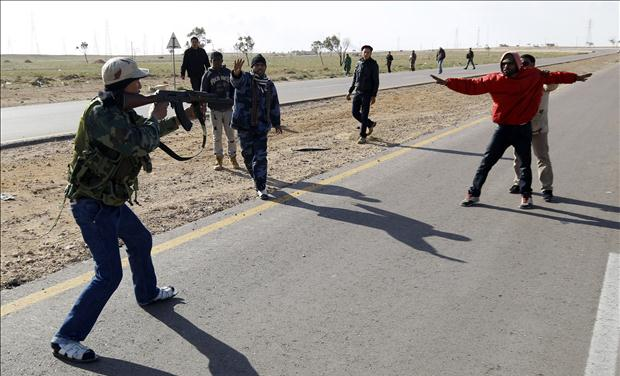Rebel fighter points his gun at suspected Gaddafi supporter as other rebels try to protect suspected supporter, on road between Benghazi and Ajdabiyah, near Ajdabiyah