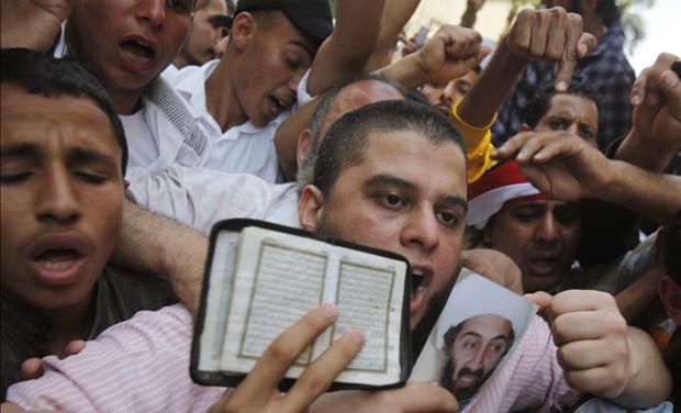 Islamists protest while holding a picture of Osama bin Laden and a copy of the Koran during a protest in Cairo