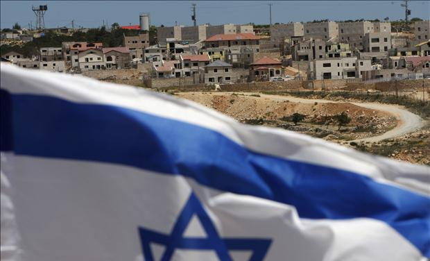 An Israeli flag waves on a hill near Elazar, in the Etzion settlement bloc