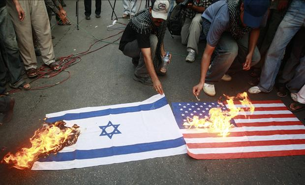 Supporters of Shi'ite Muslims burn U.S. and Israeli flags during a protest against the 61th anniversary of the foundation of the State of Israel in Karachi
