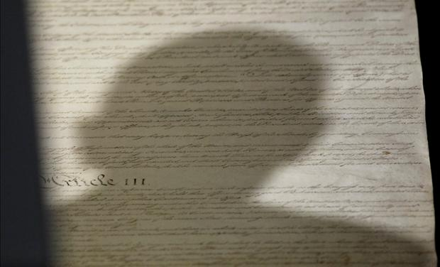 Shadow of head of U.S. President Obama falls upon copy of U.S. Constitution at National Archives in Washington