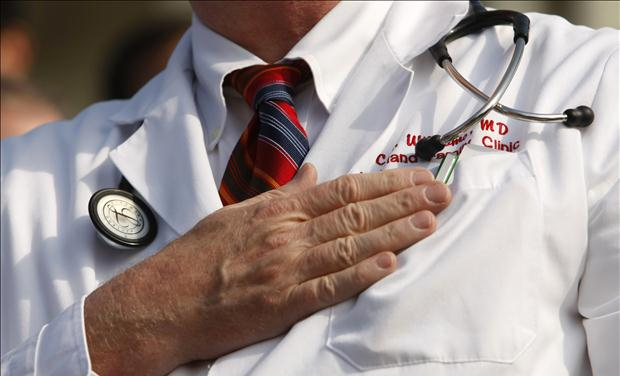 "A doctor puts his hand over his chest during a ""House call"" rally against proposed healthcare reform legislation at the Capitol in Washington"