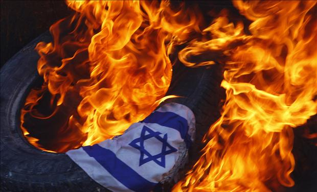 An Israeli flag burns during a protest in Nilin