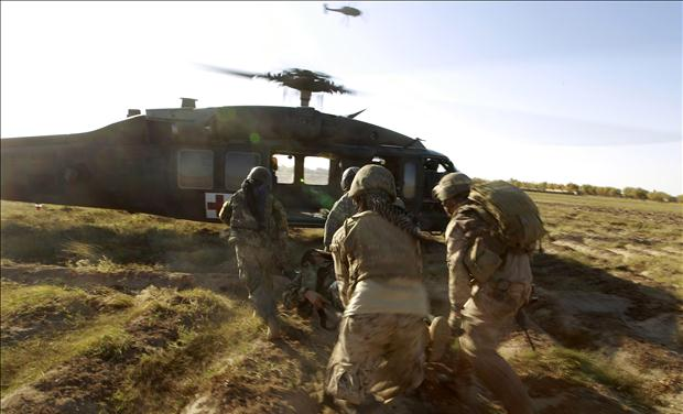 A Blackhawk helicopter from CCO., 1-214 AVN flies overhead as U.S. Marines and members of the Afghan Army carry a wounded Afghan soldier to a helicopter during a Medevac mission in southern Afghanistan's Helmand province