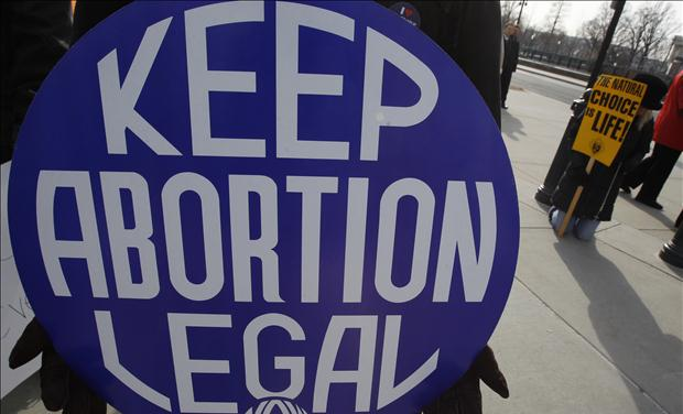 A pro-choice supporter carries a placard near a pro-life supporter during a demonstration in Washington