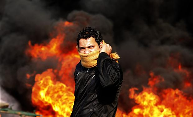 A protester stands in front of a burning barricade during a demonstration in Cairo
