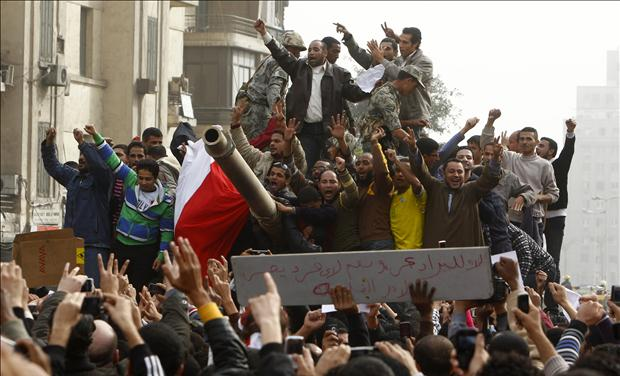 Demonstrators celebrate atop an army tank in Tahrir square during protests in Cairo